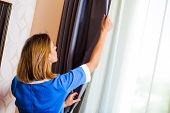 pic of maids  - Image of maid fixing the curtain in hotel room - JPG