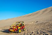 stock photo of buggy  - Dune buggy at the foot of a large sand dune in Huacachina Peru - JPG