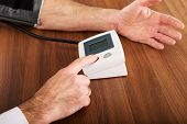 Picture of closeup on businessman measuring blood pressure.