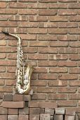 picture of lonely  - Lone old saxophone leans against brick wall outside abandoned jazz club - JPG