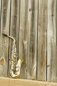 stock photo of lonely  - Lone old saxophone leans against wooden fence outside jazz club - JPG