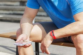 stock photo of sitting a bench  - Sportive man sits on a bench and checks his fitness results on a smartphone - JPG