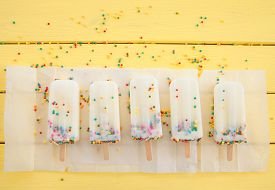 foto of sprinkling  - Homemade frozen vanilla popsicles with colorful sprinkles - JPG