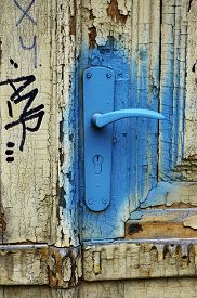 stock photo of spayed  - Old wooden door with peeling paint and a turquise spayed - JPG