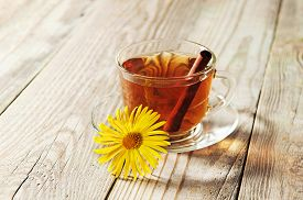 picture of black tea  - glass cup and saucer black tea with cinnamon standing on a wooden table - JPG