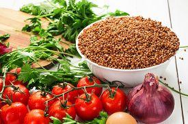 stock photo of buckwheat  - Buckwheat tomatoes onion parsley yellow eggs - JPG