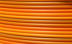stock photo of coil  - long coils of orange plastic pipes for the installation of underground utilities and energy of optical fibers - JPG