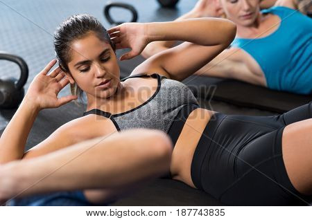poster of Young woman doing abdominal exercises in gym. Latin fit girl in fitness gym doing sit ups on the yog