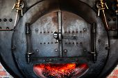 An old cast iron oven with flames viewable through the window