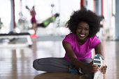 happy young african american woman in a gym stretching and warming up before workout young mab exerc poster