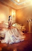 Beauty gorgeous woman in beautiful evening dress sitting and posing in Luxurious style interior room poster