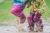 Children In Rubber Boots And Rain Clothes Jumping In Puddle. poster
