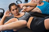 Young woman doing abdominal exercises in gym. Latin fit girl in fitness gym doing sit ups on the yog poster