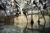 Stalactites and ground-piercing roots reflected from the clear water underground in