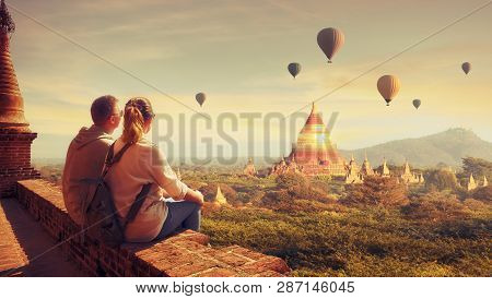 poster of Happy Tourists, Friends, Enjoy Watching The Flight Of Balloons Over The Old Bagan In Myanmar. Young