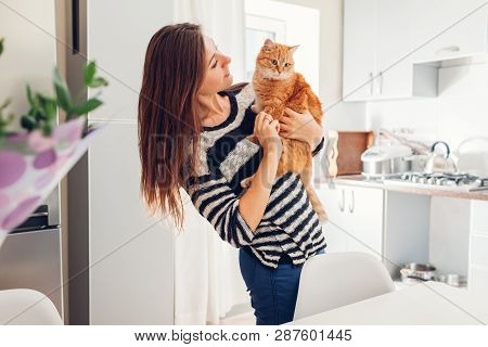 poster of Young Woman Playing With Cat In Kitchen At Home. Girl Holding And Hugging Ginger Cat