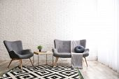 Stylish Sofa And Armchair Near Brick Wall In Modern Living Room Interior. Space For Text poster
