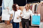 Mother And Daughter Feeling Happy And Satisfied While Leaving Shop With Bags poster
