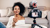 Happy Female Vlogger Live Streaming From Living Room Using Dslr Camera poster
