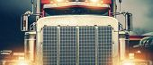 Shiny American Semi Truck On A Road. Large Chromed Grill Front View In Wide Format. Trucker On The R poster