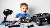 Radio Controlled Models: A Little Boy In A Blue T-shirt Is Repairing His Rc Car Buggy. poster