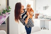 Young Woman Playing With Cat In Kitchen At Home. Girl Holding And Hugging Ginger Cat poster