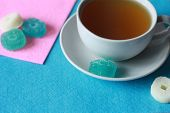 White Cup With Green Tea On A Saucer With Multi-colored Marmalade Sweets On A Pink And Blue Felt Bac poster