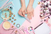 Concept Of Nail Art. Woman Gives Herself A Manicure On A White Table poster
