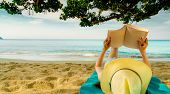 Woman Lie Down On Green Towel That Put On Sand Beach Under The Tree And Reading A Book. Slow Life On poster