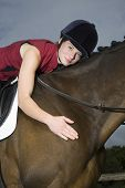 stock photo of riding-crop  - Portrait of a female horseback rider hugging a cropped brown horse - JPG
