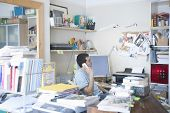 foto of untidiness  - Side view of businessman using landline phone in creative office space - JPG