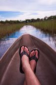 image of canoe boat man  - mans feet relaxing a canoe with an interesting point of view - JPG