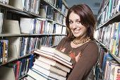 pic of shelving unit  - Female University student holding books in library portrait - JPG