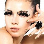 stock photo of minx  - Closeup portrait of the beautiful woman with long black false eyelashes makeup and golden nails - JPG
