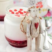 A Jar Of Yoghurt With Raspberry Jam And A Teddy Bear Toy Leaning Over It