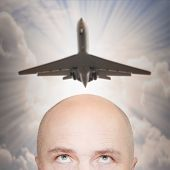 An man and passenger plane over his head. Travel and migration concept.
