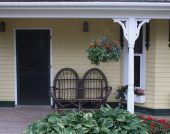 stock photo of screen-porch  - Wicker chairs sit on the front porch - JPG