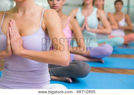 Yoga class in lotus pose in fitness studio at the leisure center