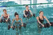 picture of day care center  - Female fitness class doing aqua aerobics with foam dumbbells in swimming pool at the leisure centre - JPG
