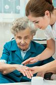stock photo of personal hygiene  - Nurse assists an elderly woman with skin care and hygiene measures at home - JPG