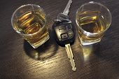 picture of whiskey  - two whiskey shots on the bar shelf with car key between them - JPG