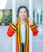 stock photo of polite girl  - Graduate Thai college girl in academic gown is holding poles and smiling happily for the moment - JPG
