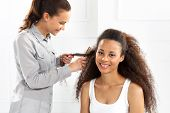 stock photo of dreads  - African woman at the hairdresser .  The dark-skinned woman in a hair salon - JPG