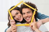stock photo of love making  - Happy Young Couple Making House Shape With Folding Ruler - JPG