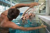 image of day care center  - Female fitness class doing aqua aerobics with male instructor in swimming pool at the leisure centre - JPG