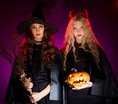 stock photo of antichrist  - Portrait of two sullen females with broom and pumpkin looking at camera - JPG
