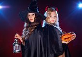 image of antichrist  - Portrait of two females with lantern and pumpkin looking at camera in the dark - JPG