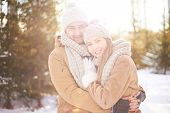 picture of amor  - Young amorous couple embracing and looking at camera outdoors - JPG