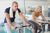 foto of exercise bike  - Determined fit young couple working on exercise bikes at the gym - JPG