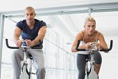 stock photo of exercise bike  - Determined fit young couple working on exercise bikes at the gym - JPG